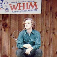 Emcee Fred Bartenstein waits for a late band onstage at the Country Gentlemen's Bluegrass Festival, Escoheag, RI. 1973 (Photo: Cole Denoncourt)